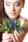Teen girl smell snowdrop flowers — Stock Photo