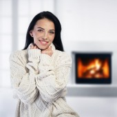 Woman relaxing by the fireplace — Stock Photo