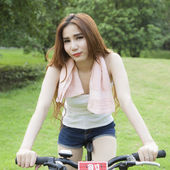 Woman riding an exercise bike in the park. — Stock Photo