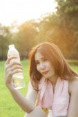 Woman Sitting and holding a bottle of water. — Stock Photo