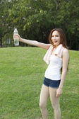 Female breaks standing and holding a bottle of water. — Stock Photo
