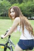 Woman riding an exercise bike in the park. — Foto de Stock