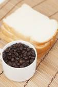 Bread plate and cup with coffee beans. — Stock Photo