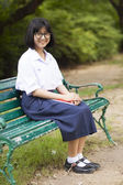 Schoolgirl. Sitting on the bench — Stock Photo
