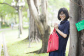 Girl wearing glasses a red holding the bag. — Stock Photo
