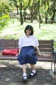 Dívka sedící na lavičce. — Stock fotografie