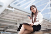 Businesswoman Sitting using a smartphone. — Stock Photo
