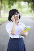 Schoolgirl standing holding a book. — Stock Photo
