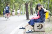 Girl wearing glasses sitting on a bench along the corridor. — Stock Photo
