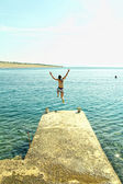 Young woman in bikini jumping from pier into sea — Stock Photo