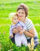 Baby girl with mother on a meadow — Stock Photo