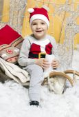 Little boy in Christmas costume sitting on a Christmas tree — Stock Photo