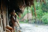 Papuan boy from Dani tribe hides from a rain under a roof. — Stock Photo