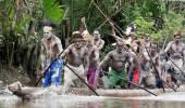 Asmat men paddling in their dugout canoe — Stock Photo