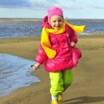 Little girl  on a sunset sandy autumn beach. — Stock Photo #73113179