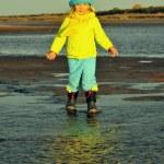 Little girl  on a sunset sandy autumn beach. — Stock Photo #73113113