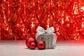 Silver present and red baubles — Stock Photo