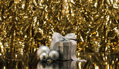 Silver present and Christmas tree baubles — Stock Photo