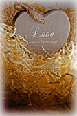 brown wooden love heart in a love nest — Stock Photo