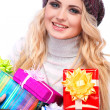 A photo of beautiful girl is in winter clothes with varicoloured gift boxes, isolated — Stock Photo #53450191