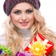 A photo of beautiful girl is in winter clothes with varicoloured gift boxes, isolated — Stock Photo #53450231