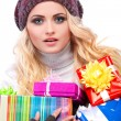 A photo of beautiful girl is in winter clothes with varicoloured gift boxes, isolated — Stock Photo #53450233