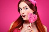 Portrait of beautiful  merry redheaded girl with a large candy on a pink background — Stock Photo