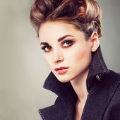 Portrait of elegant young woman in a grey overcoat  on a grey background — Stock Photo
