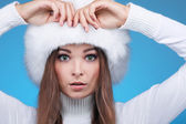Beautiful merry sexual girl in a white fur cap and warm clothes on a blue background — Stock Photo