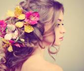 Beautiful  girl, isolated on a light - grey  background with varicoloured flowers  in hairs, emotions, cosmetics — Stock Photo