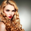 Closeup portrait of sexy  young woman with beautiful blue eyes and red lips on a grey background — Stock Photo #74483127