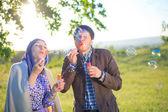 Charming couple blowing bubbles — Photo