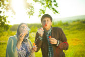 An engaged couple blows bubbles. — Stock Photo