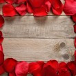 Frame of red rose petals on wooden background — Stock Photo #53714395