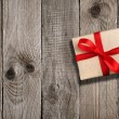 Gift box with red ribbon on wooden background — Stock Photo #55810187