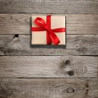 Gift box with red bow on wooden background — Stock Photo #55810223