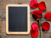 Blackboard and red rose on wooden background — Foto de Stock