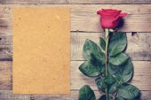 Vintage rose and blank paper on old wooden background — Stockfoto