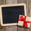 Blank blackboard and gift box on wooden background — Stock Photo #63229973