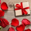 Gift box and red rose on wooden background — Stock Photo #65102981