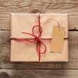 Gift box with tag close-up on wooden background — Stock Photo #69347673