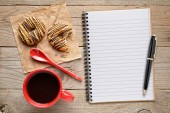 Coffee cup with cookies and notepad with pen on wooden table — Stock Photo