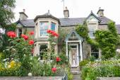 Old, British house with window and climbing roses — Stock Photo