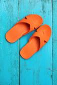Orange flip flop sandals on blue wooden background — Stock Photo