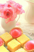 Beautiful colorful cakes and pink roses, still life  — Stock Photo