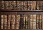 Old books in a wooden library — Stock Photo