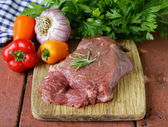 Raw beef steak with ingredients vegetables on a wooden board — Stockfoto