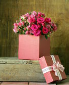 Gift box with a bouquet of roses on a wooden background — Stock Photo