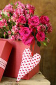 Bouquet of roses with gift box on a wooden background — Stock Photo