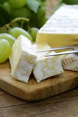 Soft brie cheese with sweet grapes on a wooden board — Stock Photo